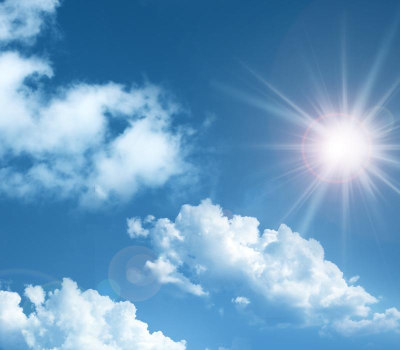 sun shining in bright blue sky with puffy clouds