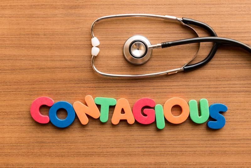 contagious colorful word on the wooden background with stethoscope