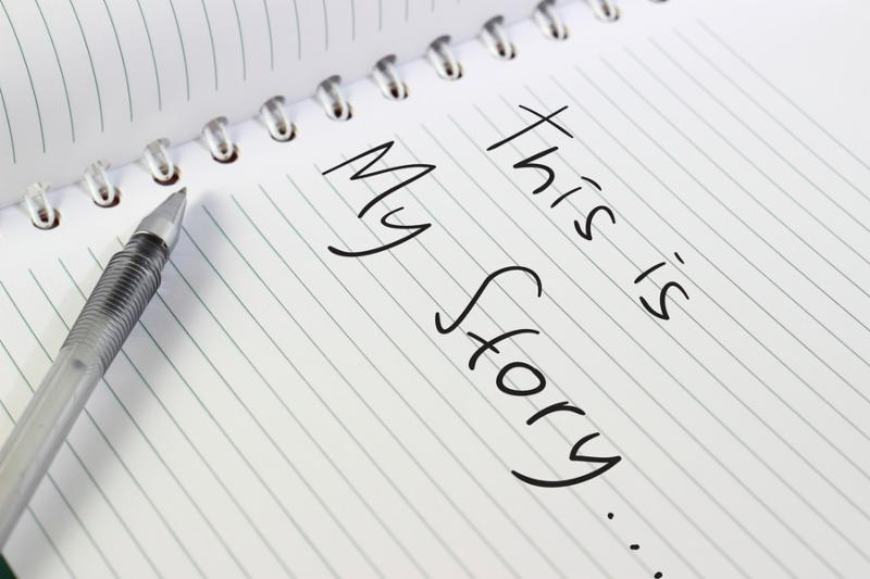 Image of opened white note book with a pen, and This Is My Story words written on it
