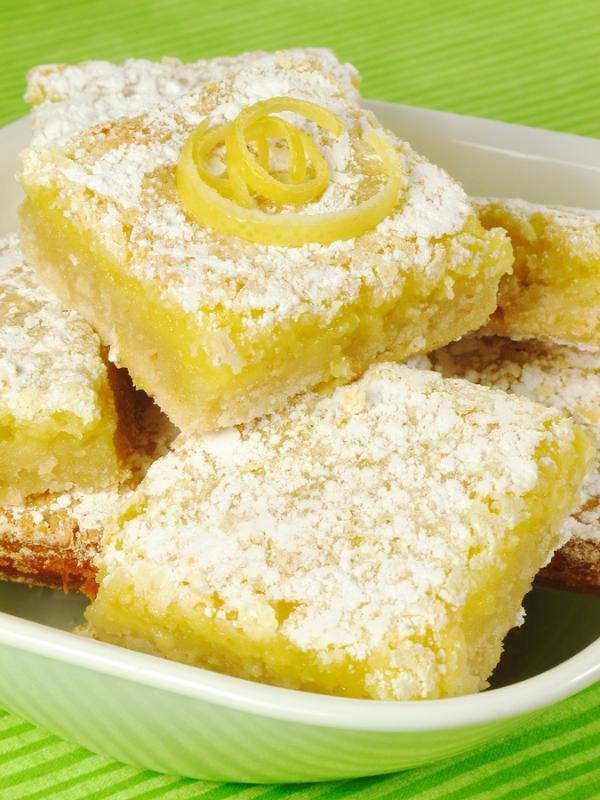 Baked lemon bars sprinkled with powdered sugar.