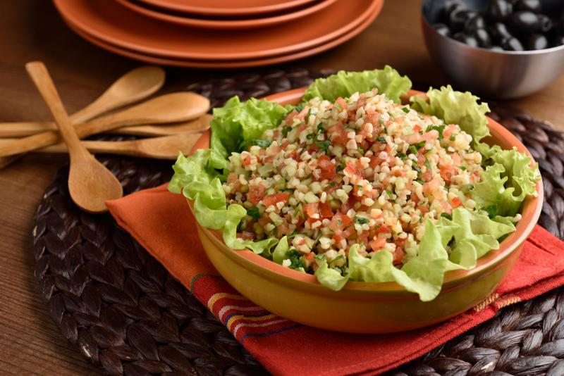 Tabbouleh with bulgur, tomatoes, parsley, and lettuce on a rustic table