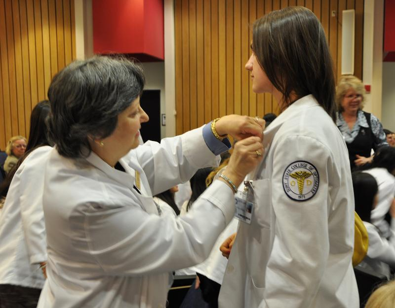 Dr. Adamczyk pins a student