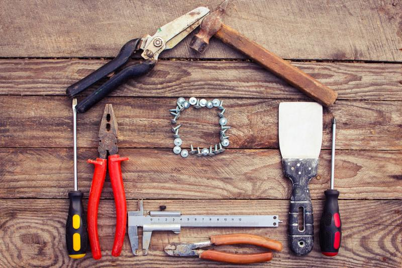Construction tools in the form of house on wooden background. construction tools  pliers, hammer, pruner, screws, putty knife and ruler.