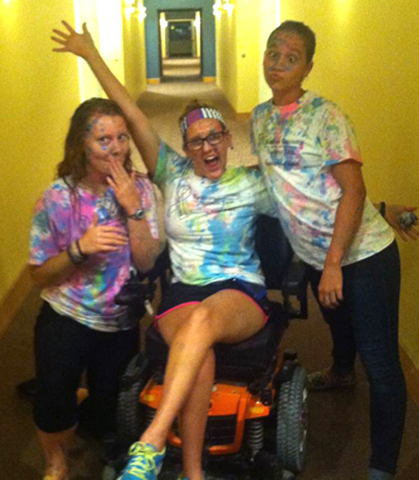 Kelsey and two friends make funny faces as they wear clothing covered in chalk