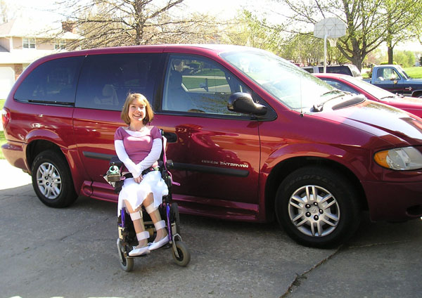 Carrie sits in front of her red van