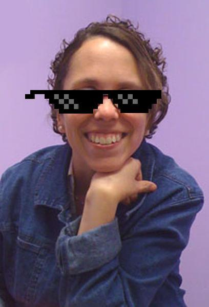 Julia Thomas with cartoon sunglasses over her face. She is smiling and has her hand under her chin.