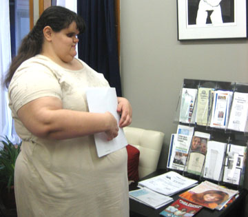 Amber reads a braille brochure in the KYEA office