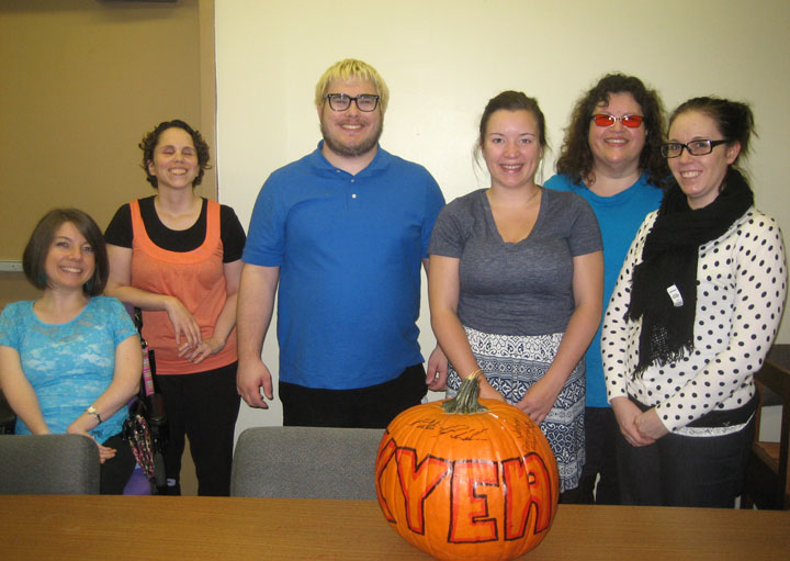 KYEA staff pose for a group photo with a pumpkin in front of them that says KYEA