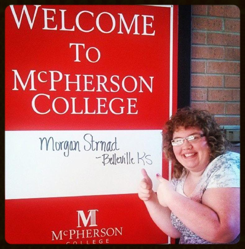 Morgan Strnad gives a thumbs up to a McPherson College sign