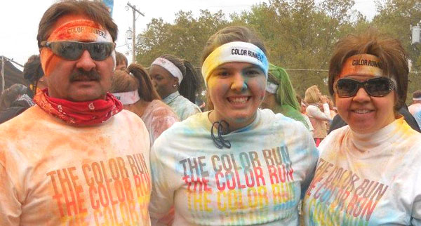 Rachel stands, covered in multiple colors, with her parents at a 5K race