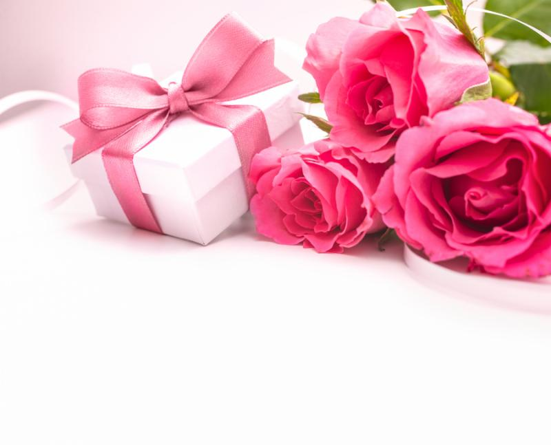 Bouquet of pink roses and gift box on white background Note Shallow depth of field