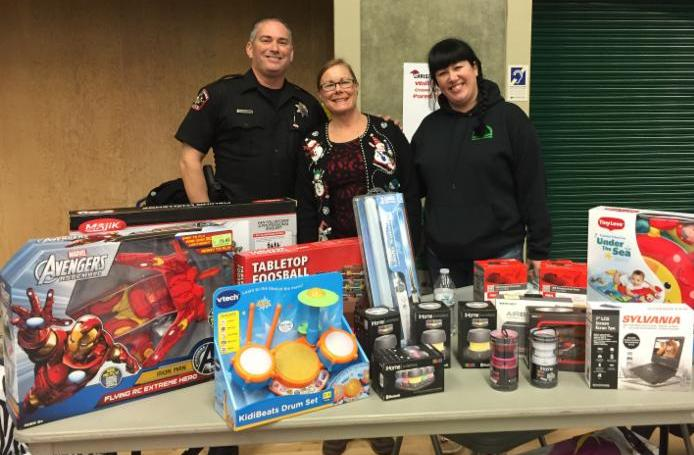 Volunteers pose with toys at the 2014 Christmas in Cordova event.