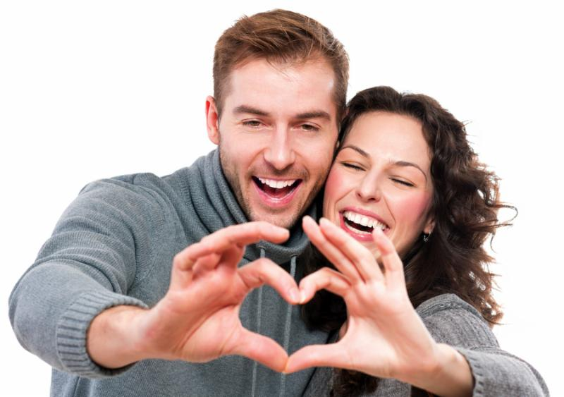 Valentine Couple. Portrait of Smiling Beauty Girl and her Handsome Boyfriend making shape of Heart