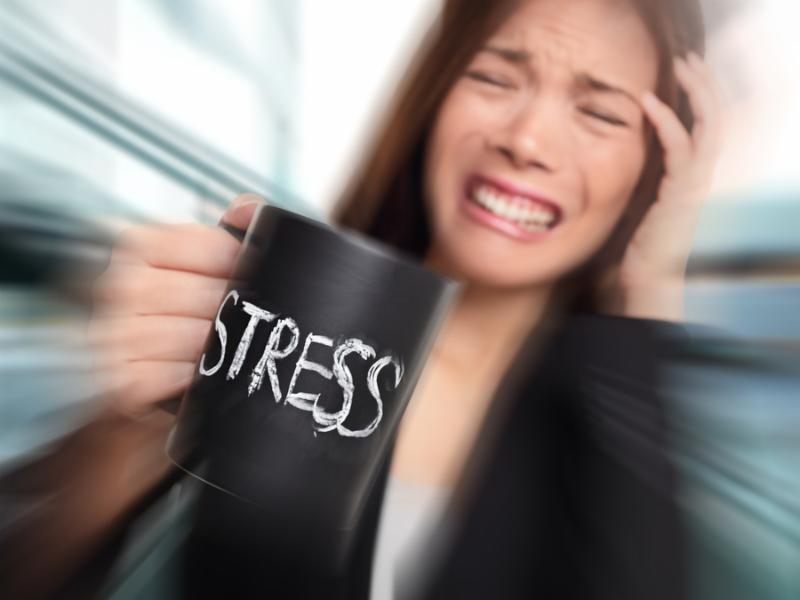 Stress - business person stressed at office. Business woman holding coffee cup with STRESS written.
