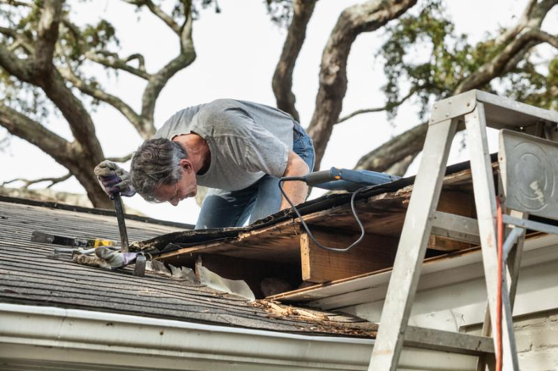 Man using crowbar to remove rotten wood from leaky roof. After removing fascia boards he has...