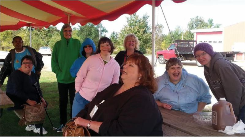 Group of women under tent awning.