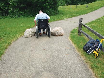 man in wheelchair on park path