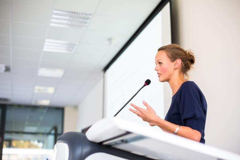 Pretty young business woman giving a presentation in a conference meeting setting  shallow DOF  color toned image