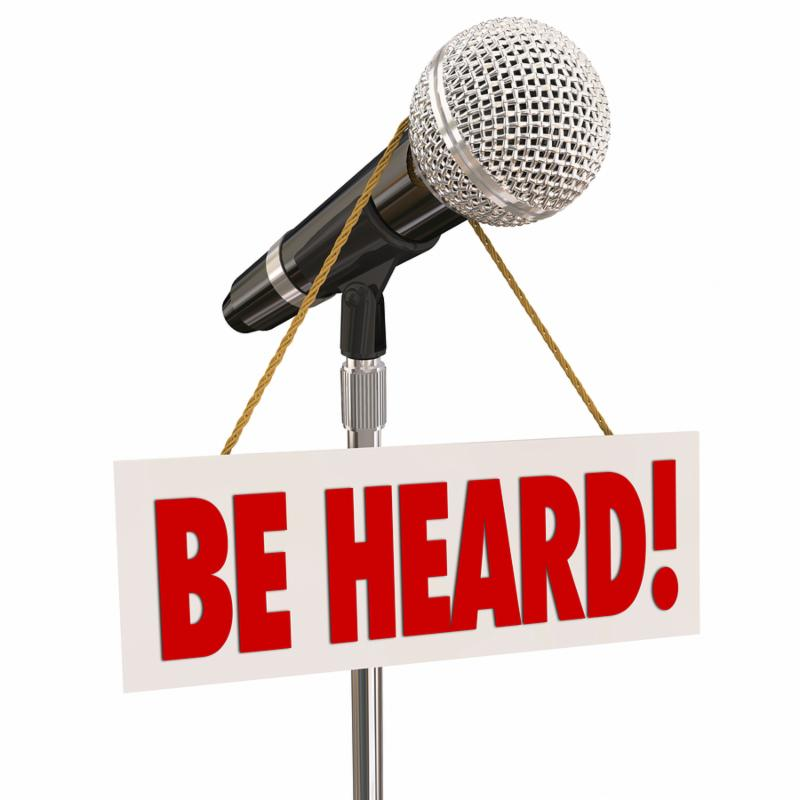 Be Heard words on a sign hanging on a microphone to illustrate sharing an opinion or viewpoint through public speaking in an open forum