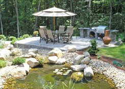 patio with outdoor kitchen and pond