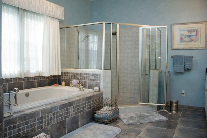 customer bath remodel in neutral gray and blue tones.