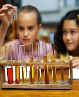 Two girls looking at test tubes