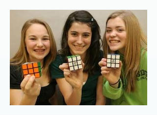 three girls holding rubiks cubes