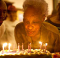 elderly woman blowing out birthday candles