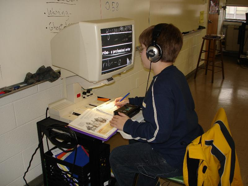 student with headphones working on computer