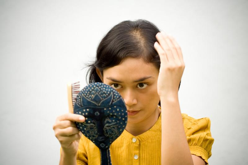 Lifestyle portrait of pretty asian young woman dressed up with hand mirror and comb on hands. curious with her hair loss