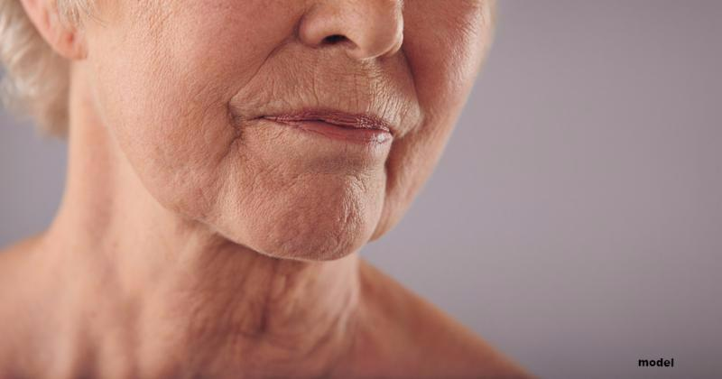 Macro of a senior female face with wrinkled skin against grey background. Cropped old woman face.     Note  Shallow depth of field