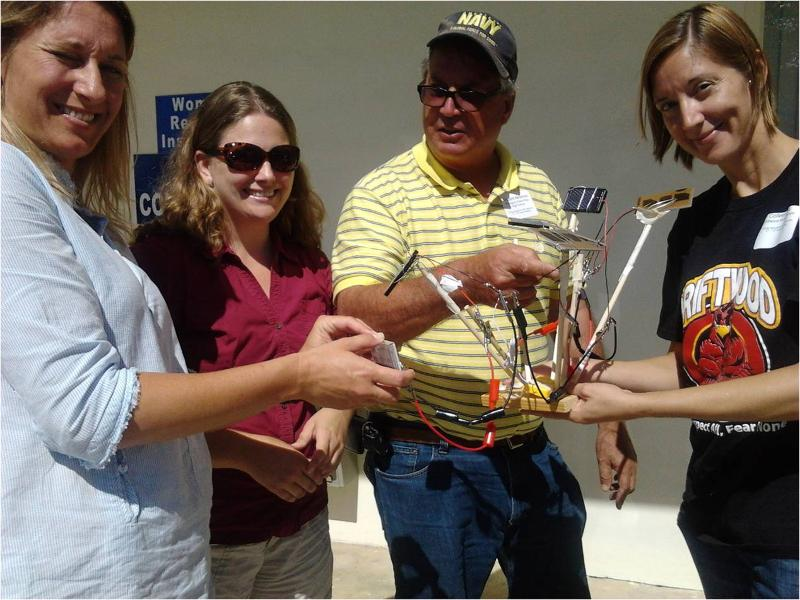 Teachers in 5th-12th grade use sun and photovoltaic cells to power small musical device at South Florida workshop in Homestead.
