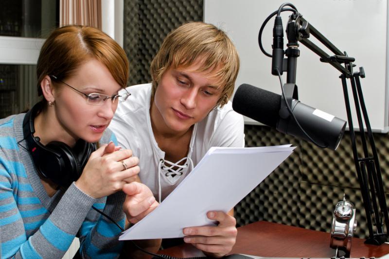 Colleagues examine broadcast list in radio studio
