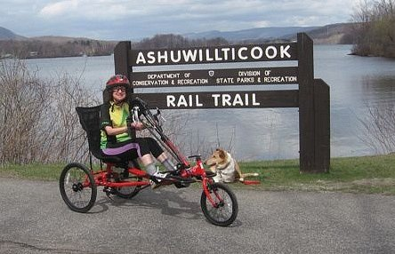 Participant smiling and seated on an adapted trike in front of Ashuwillticook Rail Trail sign (with dog).