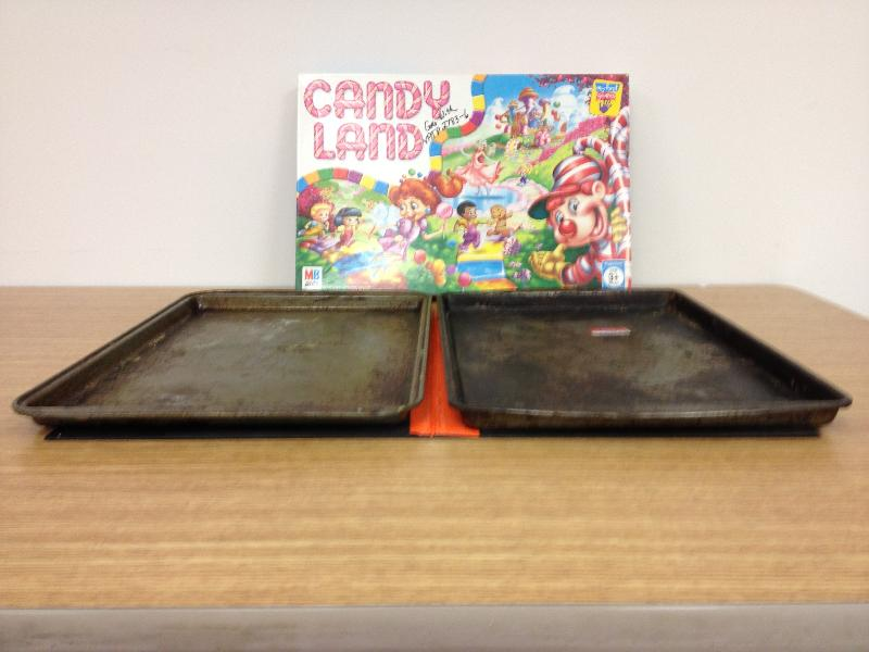 Photo of two cookie sheets and the board game Candyland.