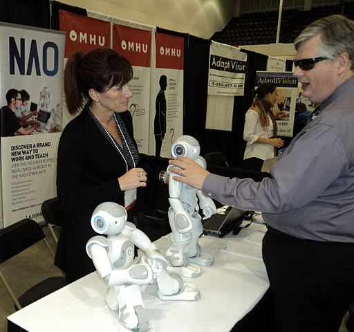 NOA robot display table with poeple admiring the product.