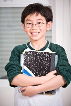Boy smiling holding school notebooks.