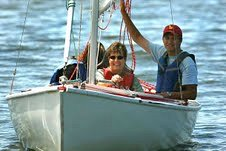 Gigi Ranno and two others sailing. Ranno is smiling, with one hand on the tiller.