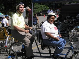 Two people on a tandam tricycle.