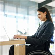 business woman in wheelchair working on laptop at a desk
