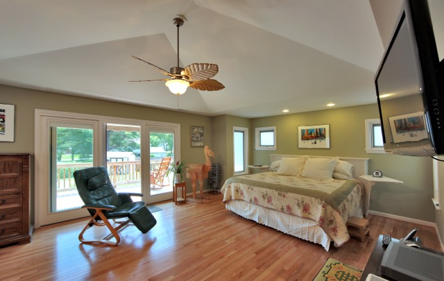 spacious master bedroom with view of rear deck and swimming pool - lots of natural light