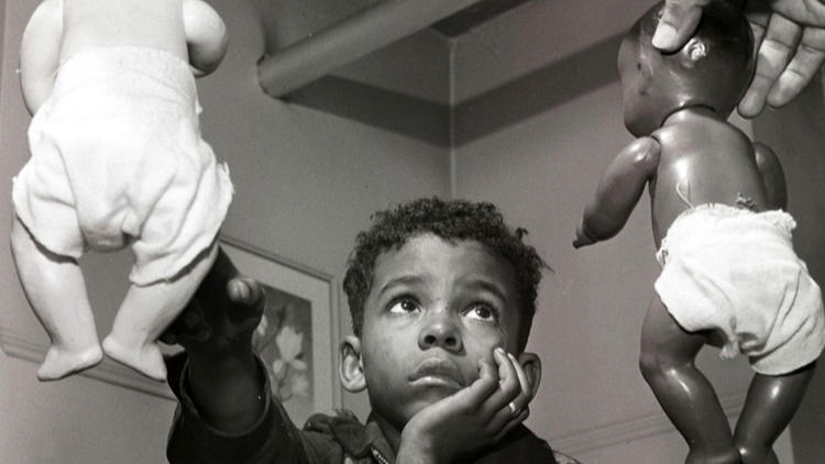 Image from the film American Denial. A boy selects a white doll as preferable to a black doll during a sociological experience.