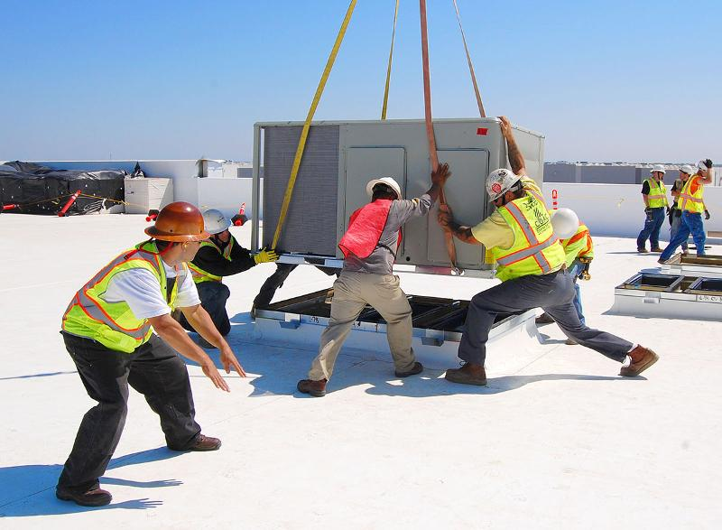 COAC Roof Crew Guides Hanging HVAC Unit onto Curb