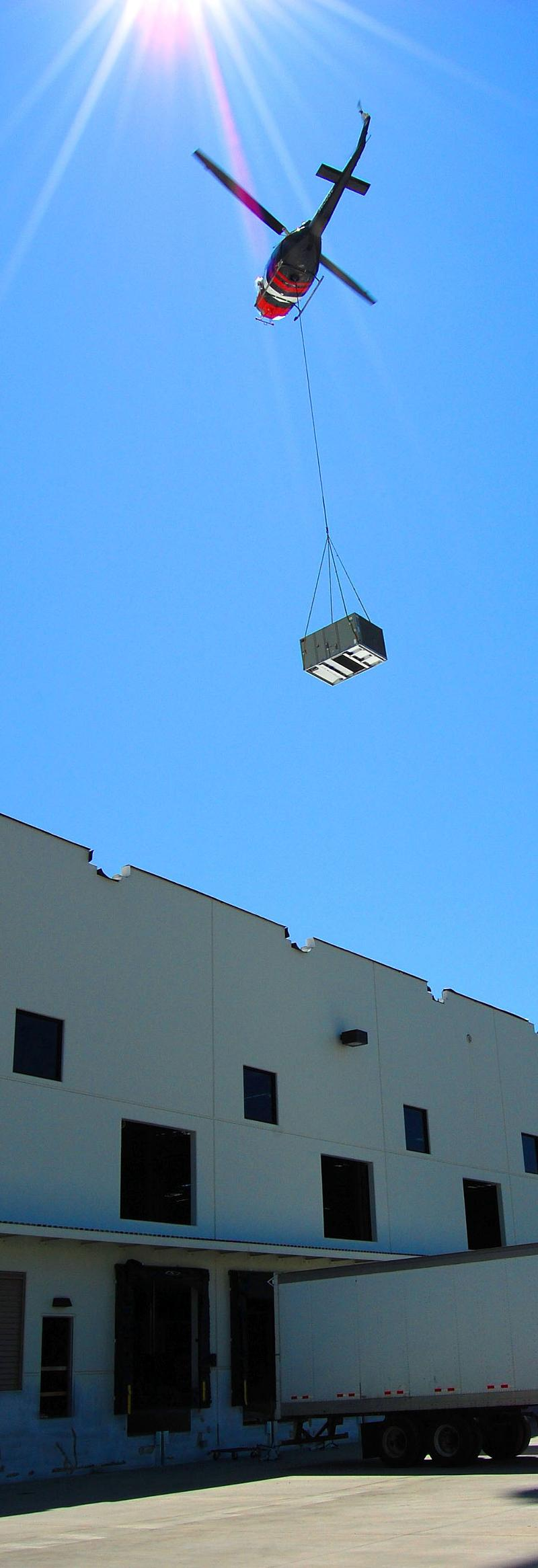 Helicopter flying HVAC Unit Over Amazon Distribution Center