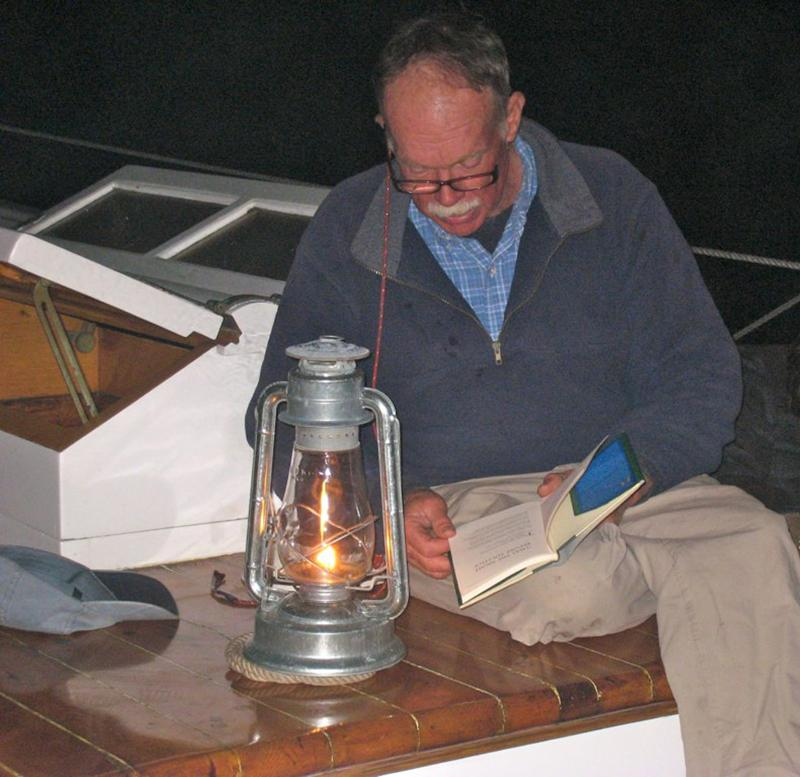 Capt John reading by lantern light