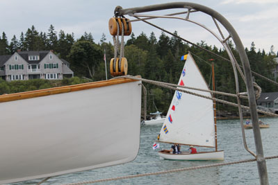 North Haven dinghies: one on the davits, one sailing by