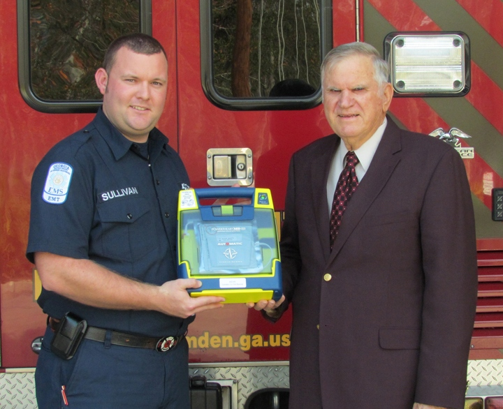 Stuart Sullivan and Chair David L. Rainer pose with an AED.