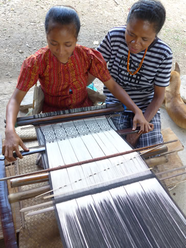 An aunt teaching her niece to weave