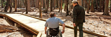 Two park rangers are shown walking along the boardwalk trail, one man is using a wheelchair while an ambulatory man is next to him.