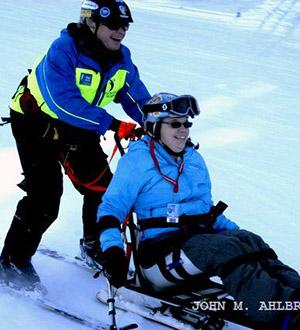 Smiles all around on a sit-ski.